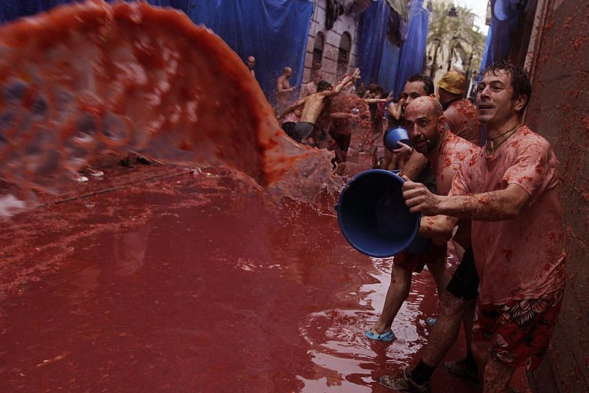 """A reveller pours tomato pulp over others after the annual """"Tomatina"""" (tomato fight) in the Mediterranean village of Buñol, near Valencia, on Aug 28, 2013. Some 20,000 revellers pelted each other with tonnes of squishy tomatoes in Spain's annual toma"""