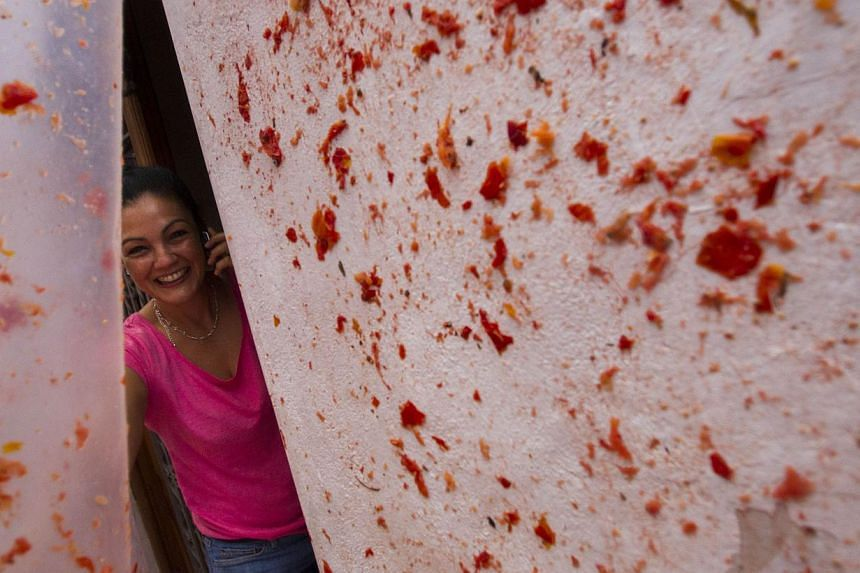 """A reveller phones as she takes part in the annual """"Tomatina"""" festivities in Buñol, near Valencia, on Aug 28, 2013. Some 20,000 revellers pelted each other with tonnes of squishy tomatoes in Spain's annual tomato fight on Wednesday - but this year th"""