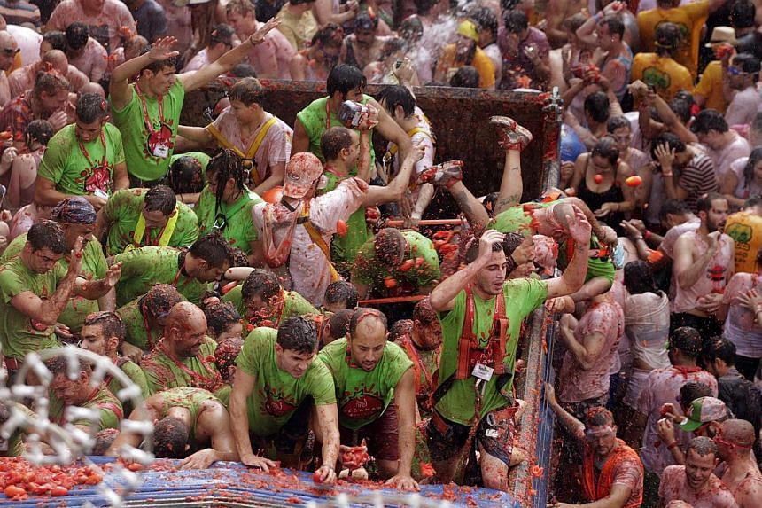 """Revellers on a truck throw tomatoes into the crowd during the annual """"Tomatina"""" (tomato fight) in the Mediterranean village of Buñol, near Valencia, on Aug 28, 2013. Some 20,000 revellers pelted each other with tonnes of squishy tomatoes in Spain's"""