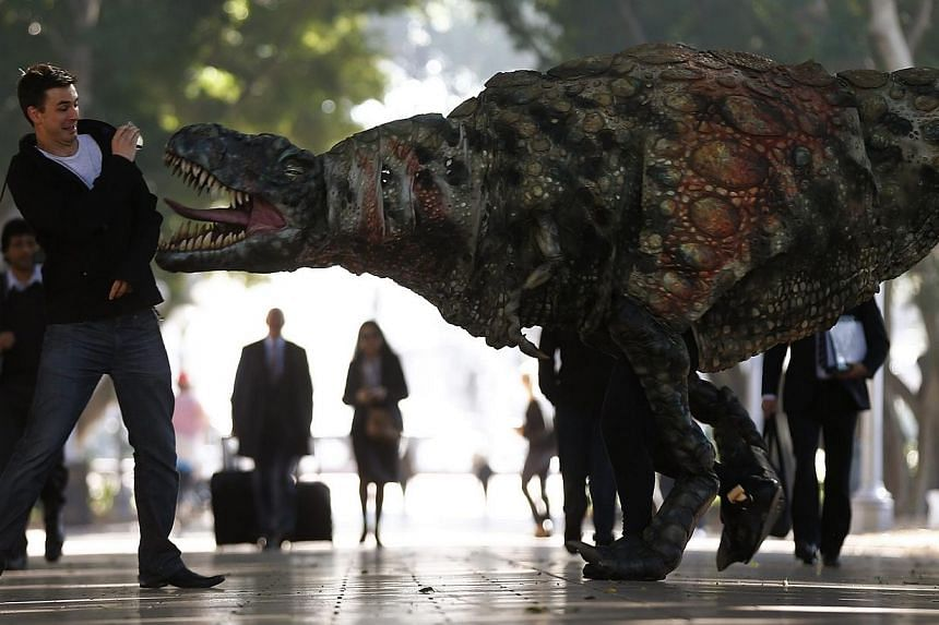 A man reacts as a performer dressed in a tyrannosaurus rex dinosaur costume walks next to him during a publicity event in central Sydney on Wednesday, Aug 28, 2013. The performance was a promotion for an upcoming exhibition at the Australian Museum t