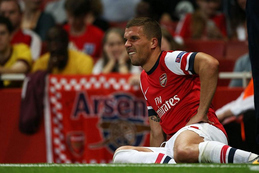 Arsenal's Polish-born German striker Lukas Podolski lies injured on the sideline during the Uefa Champions League Play-Off second leg football match at The Emirates Stadium in north London on Aug 27, 2013. Podolski will be unavailable for up to 10 we