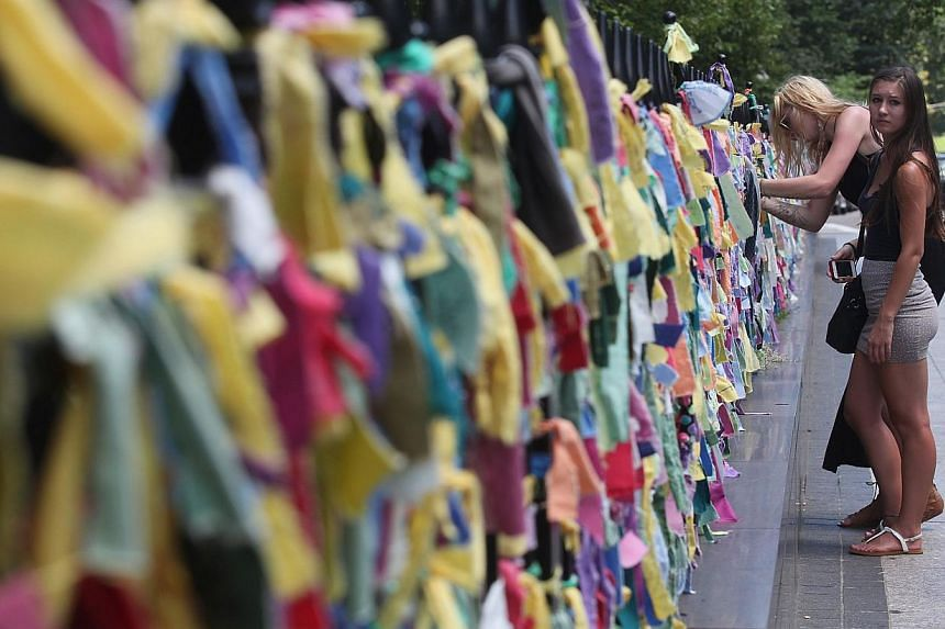 A woman attaches a prayer ribbon outside Arlington Street Church, near the site of the Boston Marathon bombings, on July 4, 2013, in Boston, Massachusetts. Chicago Marathon organisers and city officials on Thursday announced new procedures designed t