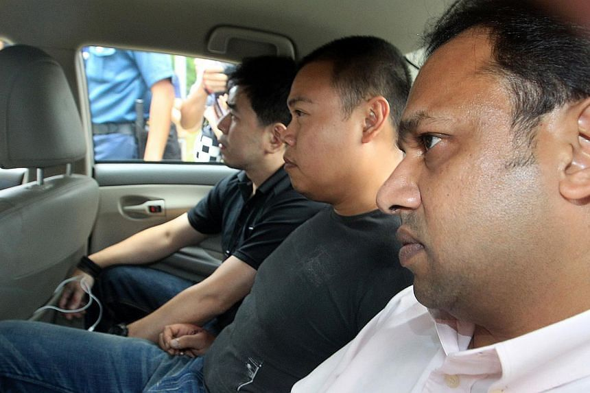 Kovan double murder suspect Iskandar Rahmat (centre) in a police car on July 13, 2013. Iskandar has been remanded for another week for further psychiatric assessment. -- ZAOBAO FILE PHOTO: WOO FL