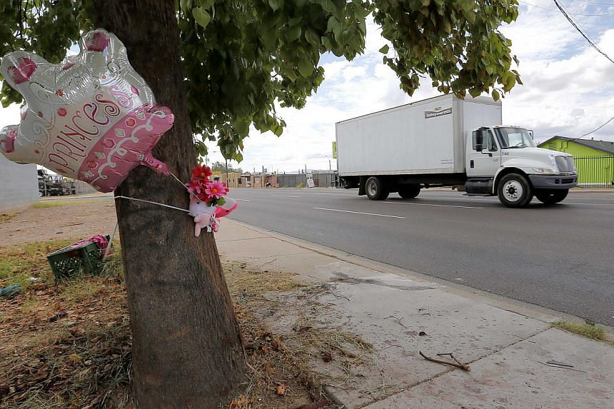 A makeshift memorial on a tree is shown, on Thursday, Aug 29, 2013, in Phoenix. An 8-year-old boy was driving his mother's car on a nighttime joyride with his 6-year-old sister when it crashed into a telephone pole, behind the tree, fatally injuring