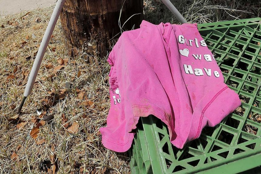 A shirt is shown by a telephone pole, on Thursday, Aug 29, 2013, in Phoenix. An 8-year-old boy was driving his mother's car on a nighttime joyride with his 6-year-old sister when it crashed into a telephone pole fatally injuring the girl, police said