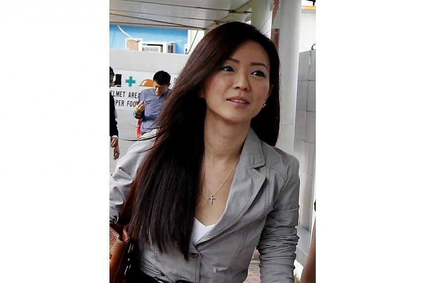 Ms Serina Wee, former finance manager of City Harvest Church (CHC), returns to court on Aug 29, 2013, with a simple yet polished look in a white dress with a grey blazer. Her ensemble is accentuated by a simple necklace with a cross pendant. -- ST PH