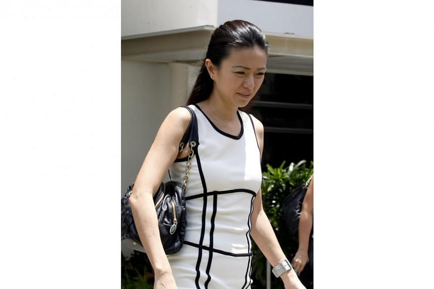 Ms Serina Wee, former finance manager of City Harvest Church (CHC), remains fashionable on Aug 30, 2013, in her white fitted dress.-- ST PHOTO:WONG KWAI CHOW