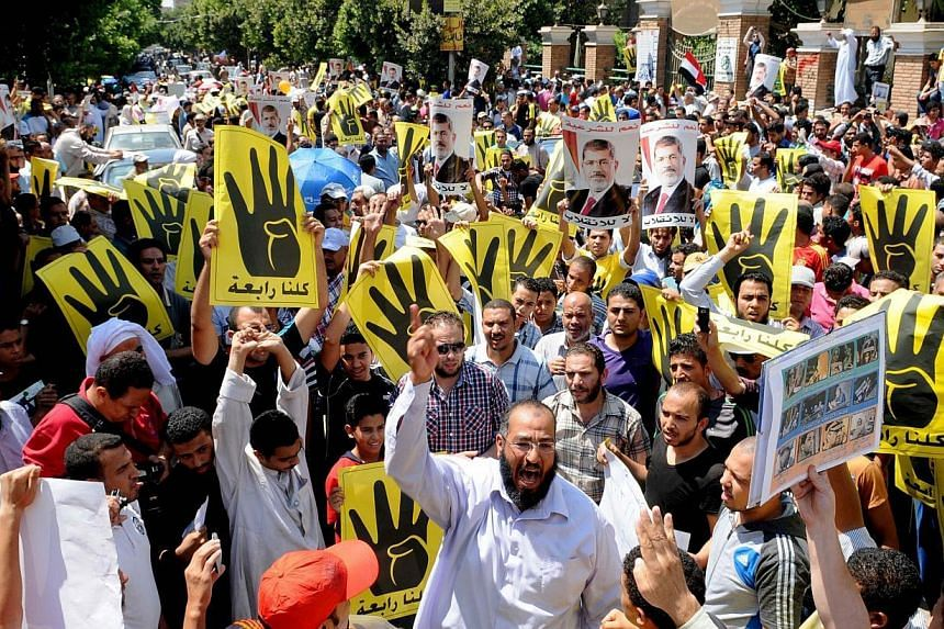 Supporters of the Muslim Brotherhood and Egypt's toppled president Mohamed Mursi take part in a demonstration in Hilwan, south of Cairo on Friday, Aug 30, 2013. Several thousand Egyptians protested in Cairo on Friday in support of ousted president Mo
