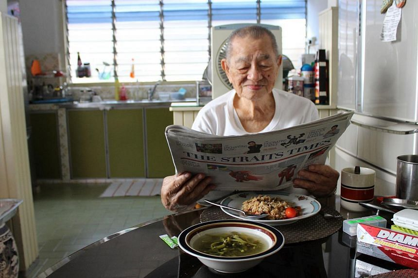 Mr Wee Thian Lee enjoys The Straits Times, with a simple home-cooked meal of fried rice and spinach soup on the dining table. This photo won third prize in The Straits Times' Wherever You Are photo contest. -- PHOTO: SELINA WEE SU LIN