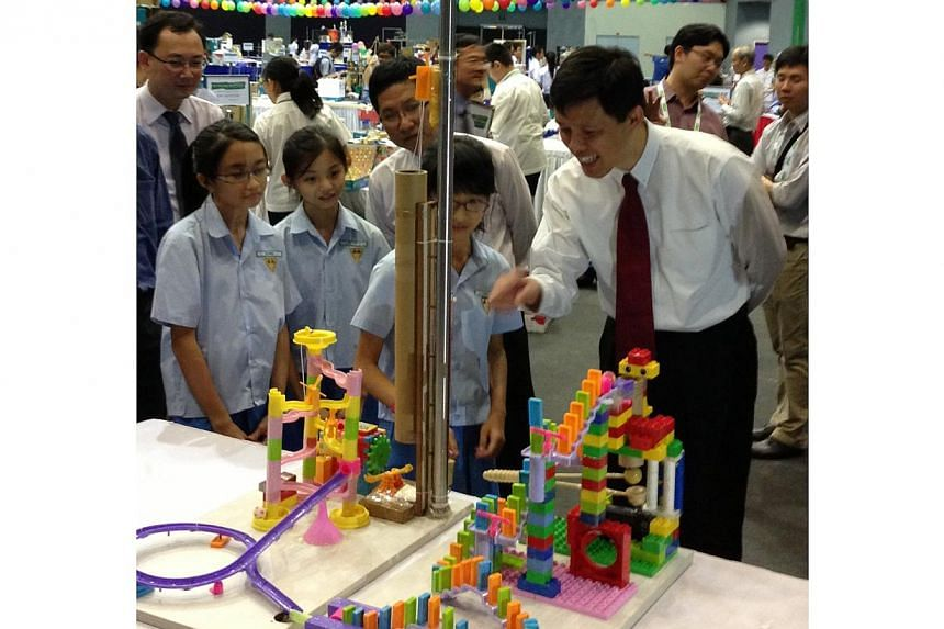 Acting Minister for Social and Family Development and Senior Minister of State for DefenceChan Chun Sing (right) checks out the winning machine from Category A (Pri 4-6) of the fourth annual Singapore Amazing Machine Competition. Creators (from