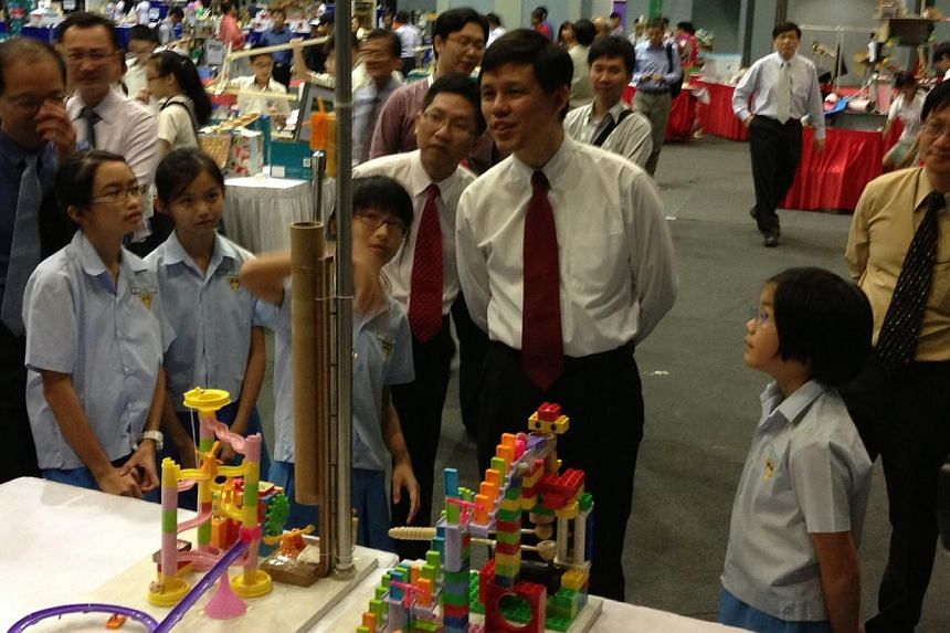 (Students from left) Rena Ho, Lee Wen Yi, Tania Neo and Tiang Tze Ling, all 11, the winning team in Category A (Pri 4-6), explain their machine to Acting Minister for Social and Family Development and Senior Minister of State for DefenceChan Ch
