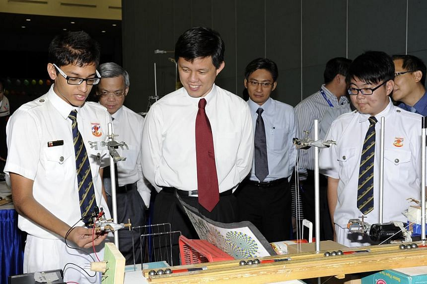 Fuhua Secondary students Ozair Hasan (left), 15, and James Ng(right), 15, share their winning Quantum-X machine with Acting Minister for Social and Family Development and Senior Minister of State for DefenceChan Chun Sing (centre). About
