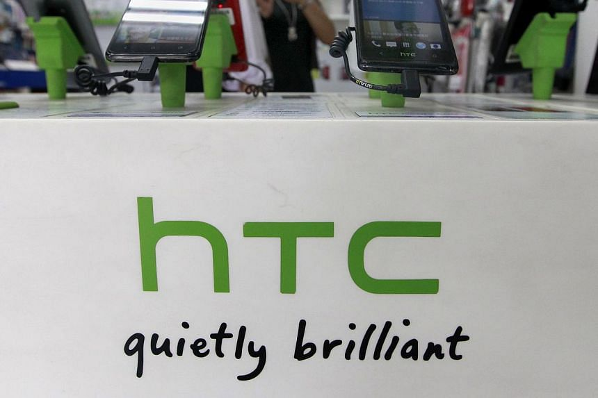 Customers look at HTC smartphones in a mobile phone shop in Taipei on July 30, 2013. Taiwanese prosecutors are investigating allegations that three employees at leading smartphone maker HTC stole trade secrets to sell to Chinese firms, reports said o
