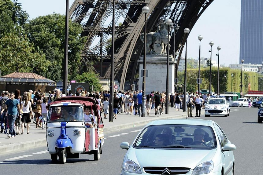 A picture taken on Aug 20, 2011 shows tourists riding on a tuk-tuk (auto rickshaw) past the Eiffel Tower in Paris. The humble tuk-tuk, a fixture in Asian cities from Bangkok to Bangalore, is rapidly becoming a common sight in the touristy parts of Pa