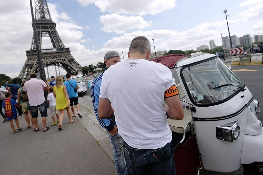 A police officer checks the identification of a tuk-tuk driver on Aug 14, 2013 near the Eiffel Tower in Paris. The tuk-tuk, a mode of public transportation found commonly in Southeast Asian countries like Bangkok and Phnom Penh, is becoming an increa