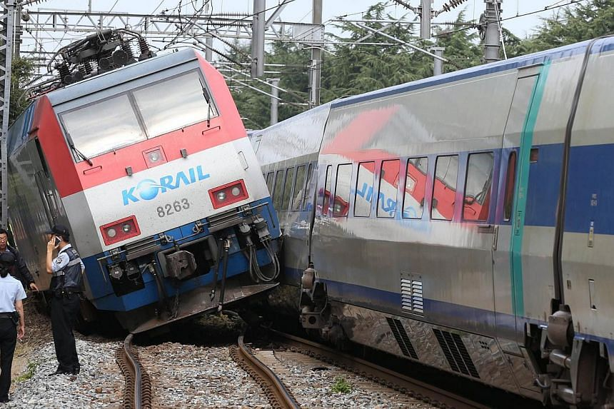 Train officers inspect the damaged parts of the trains at Daegu station in Daegu, south of Seoul on Aug 31, 2013. A collision between a bullet train and a local passenger train paralysed a key South Korean rail artery, transport officials said, but t