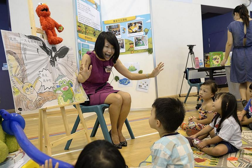 Chinese language teacher Mdm Zheng Ying Jiang tells a story from a book developed by the Ministry of Education (MOE) to children. Children enrolled in five new kindergartens run by the MOE will learn through stories, songs and dances with a dist