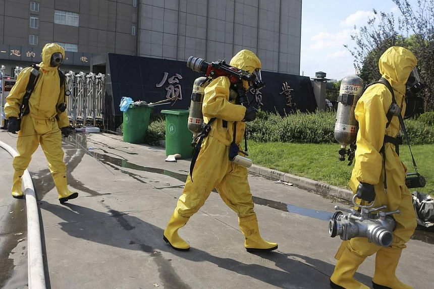 Rescuers in chemical protection suits walk outside a refrigeration unit of Shanghai Weng Pai Cold Storage Industrial Co, in the Baoshan district of Shanghai, on Saturday, Aug 31, 2013. A liquid ammonia leak from the refrigeration unit killed 15