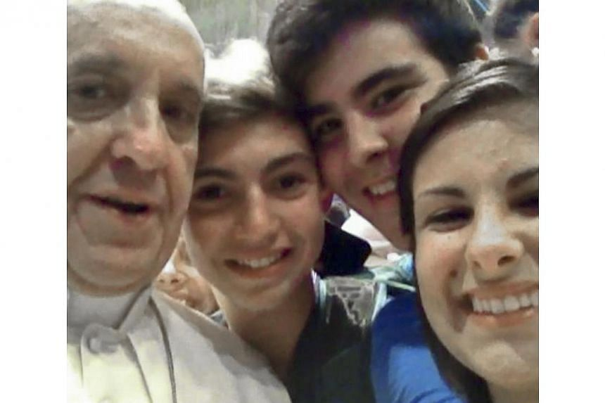 In this Wednesday, Aug 28, 2013, photo released on Friday by Miss Deborah Arcelli and taken on a mobile phone by her son Riccardo (second from left), Pope Francis (left) has his picture taken inside St Peter's Basilica witha group of teenagers