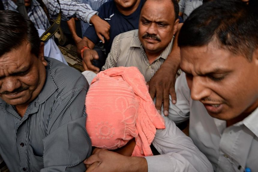 Indian policemen escort the teenager (centre, in pink hood) accused in the December 2012 gang-rape of a student to a court in New Delhi on Saturday, Aug 31, 2013. An Indian court found the teenager guilty on Saturday over the fatal gang-rape, a