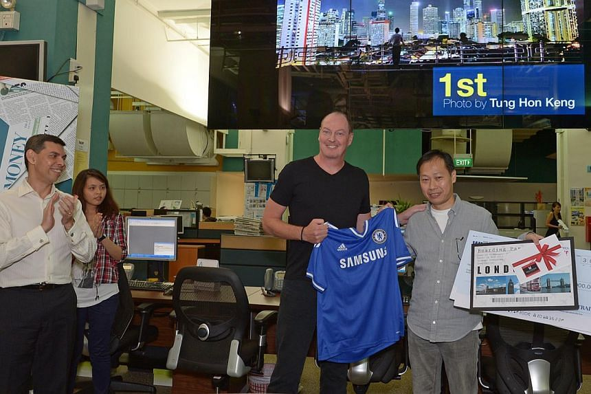 Mr Tung Hon Keng holding up a Chelsea jersey with Mr Adrian New, managing director of Chelsea Football Club in Asia. Mr Tung captured his winning image - shown above him - from the carpark of Pearl Centre. -- ST PHOTOS: DESMOND WEE