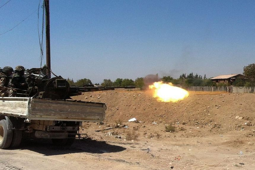 """Syrian troops fire a heavy machine gun mounted on a pickup truck in the Eastern Ghouta area on the north-eastern outskirts of Damascus on Friday, Aug 30, 2013.Syria expects a military attack """"at any moment"""", a security official told AFP on Satu"""