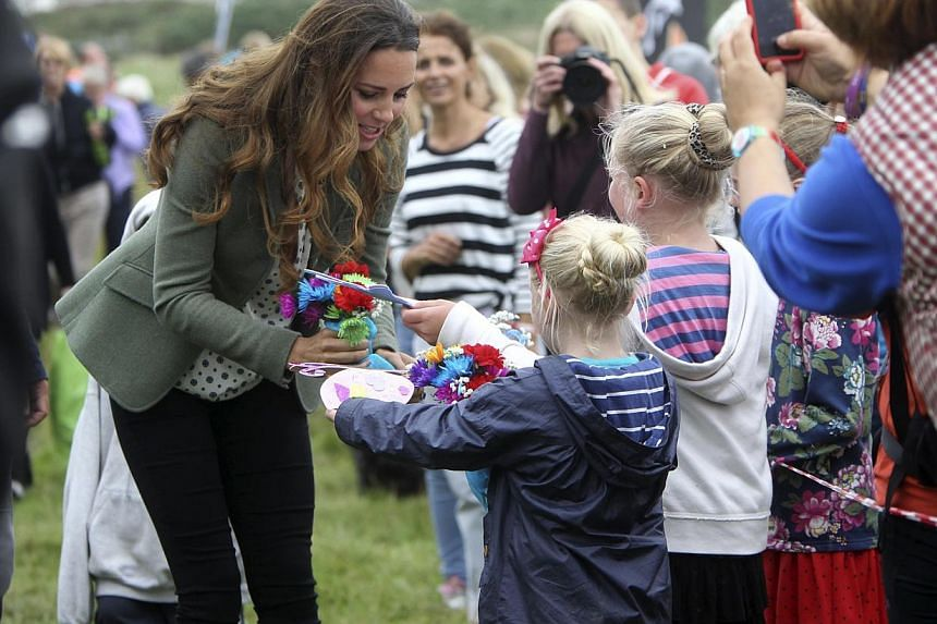 Britain's Kate, Duchess of Cambridge receives cards from wellwishers during her visit to the Breakwater country park, to start the Ring O Fire ultra marathon, in Anglesey, north Wales Aug 30, 2013. -- PHOTO: REUTERS