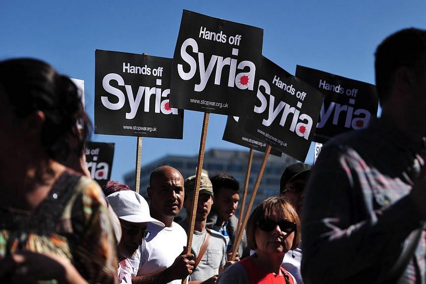 """Protesters hold signs during a protest against military intervention in Syria in central London on Aug 31, 2013. More than a thousand anti-war protesters rallied in London's Trafalgar Square on Saturday to proclaim """"victory"""" after Britain's parliamen"""