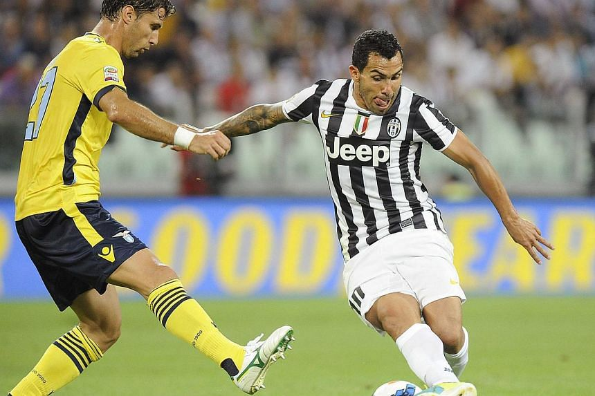Juventus' Carlos Tevez (right) is challenged by S.S. Lazio's Lorik Cana during their Italian Serie A soccer match at the Juventus stadium in Turin on Aug 31, 2013. Tevez scored his second Serie A goal in as many weeks as champions Juventus thumped La