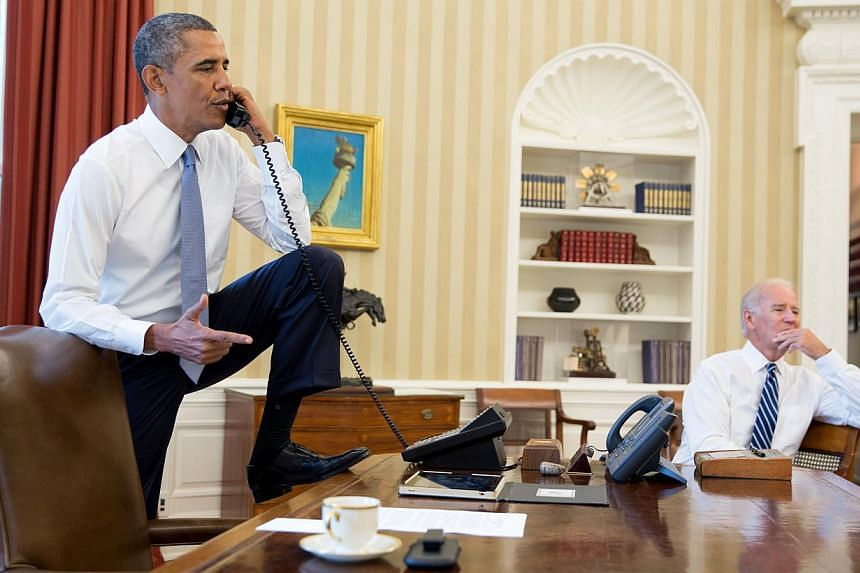 In this image released by The White House, US President Barack Obama talks on the phone in the Oval Office with Speaker of the US House of Representatives John Boehner, Republican from Ohio, on Aug 31, 2013, as Vice President Joe Biden listens. The U
