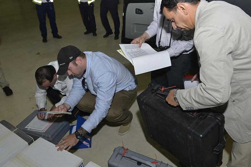 In this photo released on Saturday Aug 31, 2013 by the Organization for the Prohibition of Chemical Weapons, samples brought back by the UN chemical weapons inspection team are checked in upon their arrival at The Hague, Netherlands. The UN vowed on