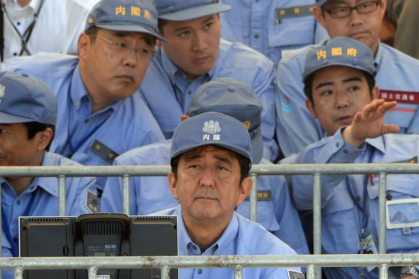 Japan's Prime Minister Shinzo Abe (front centre) watches a joint disaster prevention drill in Chiba on Sunday, Sept 1, 2013.More than one million Japanese took part in a national disaster drill on Sunday as the country assessed its emergency re