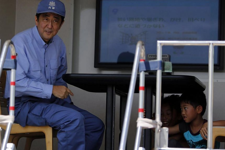 Japan's Prime Minister Shinzo Abe (left) gestures as other participants take shelter under a table inside a shaking earthquake simulator during an annual anti-disaster drill based on scenarios of a major earthquake hitting Chiba, west of Tokyo o