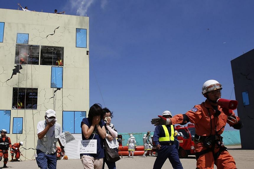 A rescue worker directs mock evacuees away from a building, which has smoke rising from it, during an annual anti-disaster drill based on scenarios of a major earthquake hitting Chiba, east of Tokyo on Sunday, Sept 1, 2013. More than one million