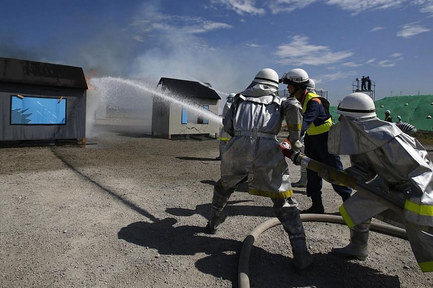 Firefighters spray water onto mock buildings that are on fire during an annual anti-disaster drill based on scenarios of a major earthquake hitting Chiba, east of Tokyo on Sunday, Sept 1, 2013. More than one million Japanese, including Prime Min