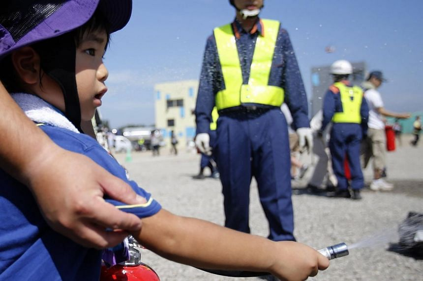 A young boy sprays water onto a flag, which is on fire, during an annual anti-disaster drill based on scenarios of a major earthquake hitting Chiba, east of Tokyo on Sunday, Sept 1, 2013.More than one million Japanese, including Prime Minister