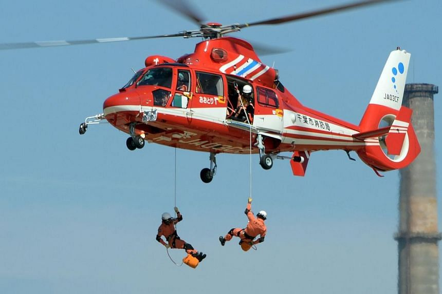 Rescue workers rappel from a fire department helicopter during a joint disaster prevention drill in Chiba, east of Tokyo on Sunday, Sept 1, 2013.More than one million Japanese, including Prime Minister Shinzo Abe, took part in a national disast