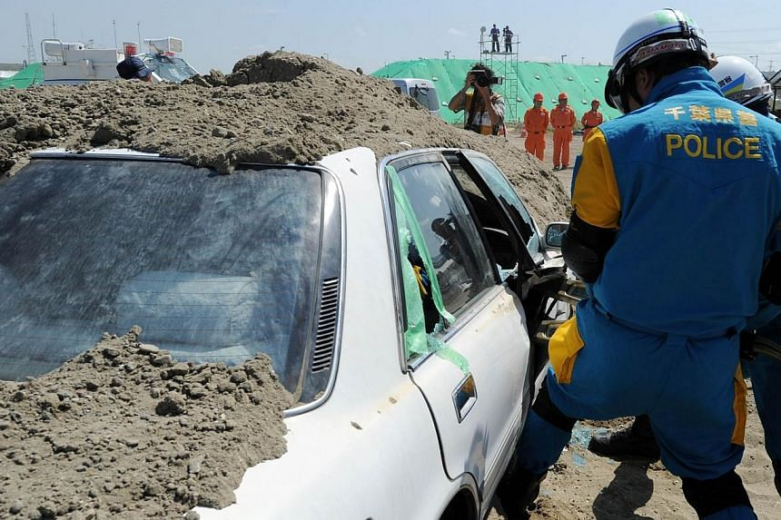 Police officers attempt to open the door of a buried car during a joint disaster prevention drill in Chiba, east of Tokyo on Sunday, Sept 1, 2013. More than one million Japanese, including Prime Minister Shinzo Abe, took part in a national disas