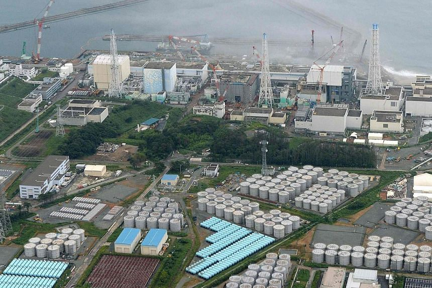 An aerial view shows Tokyo Electric Power Co's (Tepco) tsunami-crippled Fukushima Daiichi nuclear power plant and its contaminated water storage tanks (bottom) in Fukushima on Aug 20, 2013.Radiation near a tank holding highly contaminated water