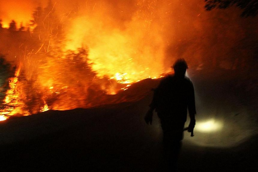 A firefighter uses a headlamp at the Rim Fire at night in this undated United States Forest Service handout photo near Yosemite National Park, California, released to Reuters Aug 30, 2013. -- PHOTO: REUTERS
