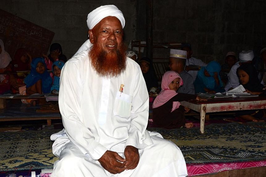 Mr Abul Nasir, 61, a Muslim Rohingya community leader in Ranong, southern Thailand. In the background are Rohingya children who come to take religious classes at a school he runs in the compound of his home. -- ST PHOTO: TAN HUI YEE
