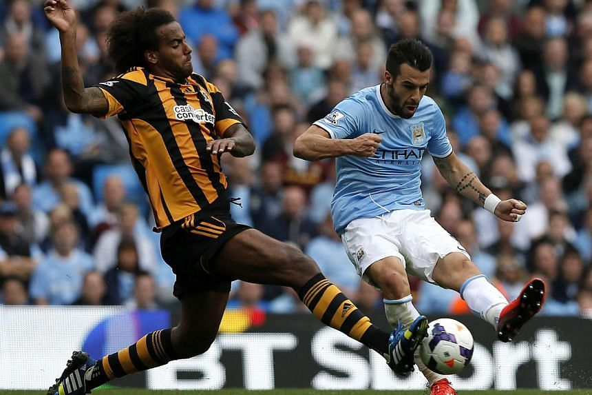 Manchester City's Alvaro Negredo (right) is challenged by Hull City's Tom Huddlestone during their English Premier League football match at The Etihad Stadium, Manchester northern England Aug 31, 2013. -- PHOTO: REUTERS