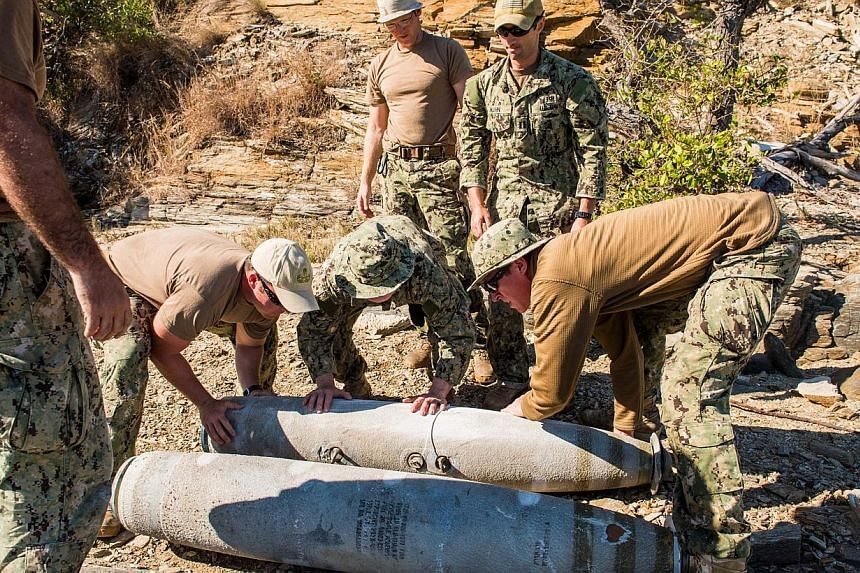 This photo released by the US Navy on Aug 30, 2013 and received on Sept 1, 2013, shows five members of Explosive Ordnance Disposal Mobile Unit (Eodmu) placing recovered ordnance from the Great Barrier Reef Marine Park area at the disposal site near t