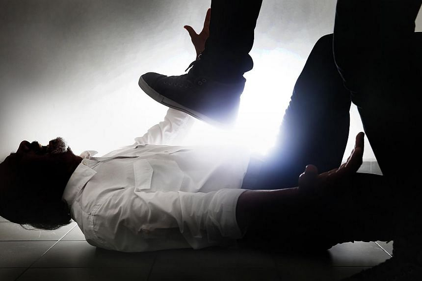 Posed photo of a man lying on the floor while a person pretends to stamp on his chest. A young woman who was part of a vice ring pleaded guilty on Monday to grievously hurting a Caucasian customer and drug-taking. -- THE NEW PAPER PHOTO:GARY GO
