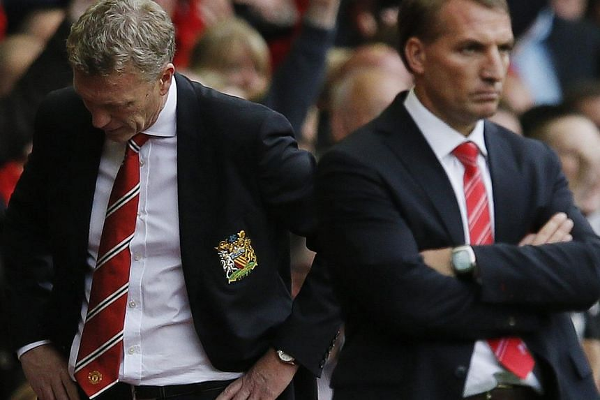 Manchester United's manager David Moyes (left) reacts as Liverpool's manager Brendan Rodgers watches their English Premier League soccer match at Anfield, Liverpool, northern England on Sept 1, 2013.Despite defeat by Liverpool and an injury to
