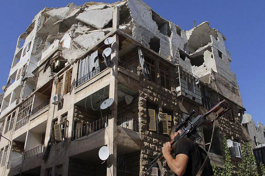 A Free Syrian Army fighter walks with his weapon in front of a damaged building in Aleppo's Al-Ezaa neighbourhood, Sept 1, 2013. The nuclear-powered aircraft carrier USS Nimitz and other ships in its strike group are heading west towards the Red