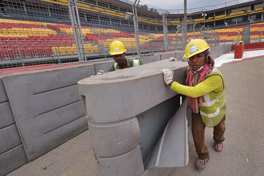 Workers set up barriers at Turn 1 of the Singapore GP race route. -- STPHOTO:MUGILAN RAJASEGERAN