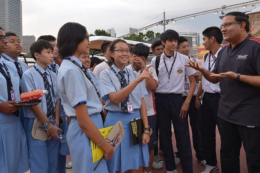 Minister, Prime Minister's Office, Second Minister for Home Affairs and Second Minister for Trade and Industry S Iswaran (right) chats with students from Woodlands Secondary and Montfort Secondary during an exclusive behind-the-scenes peekat li