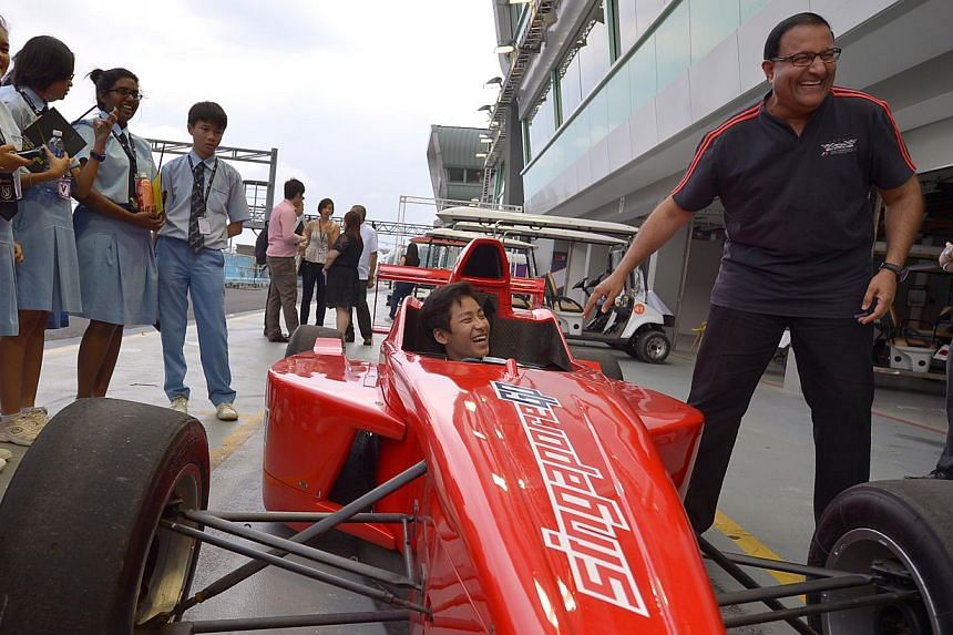 Minister, Prime Minister's Office, Second Minister for Home Affairs and Second Minister for Trade and IndustryS Iswaran (right)reacts as Montfort Secondary student Theodore Bui, 15, sits in a Formula BMW car, which is now used for extrica