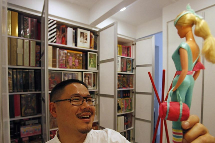 Doll collector Jian Yang talks about the first doll (right) that started his collection at his home in Singapore on Monday, Sept 2, 2013. -- PHOTO: REUTERS